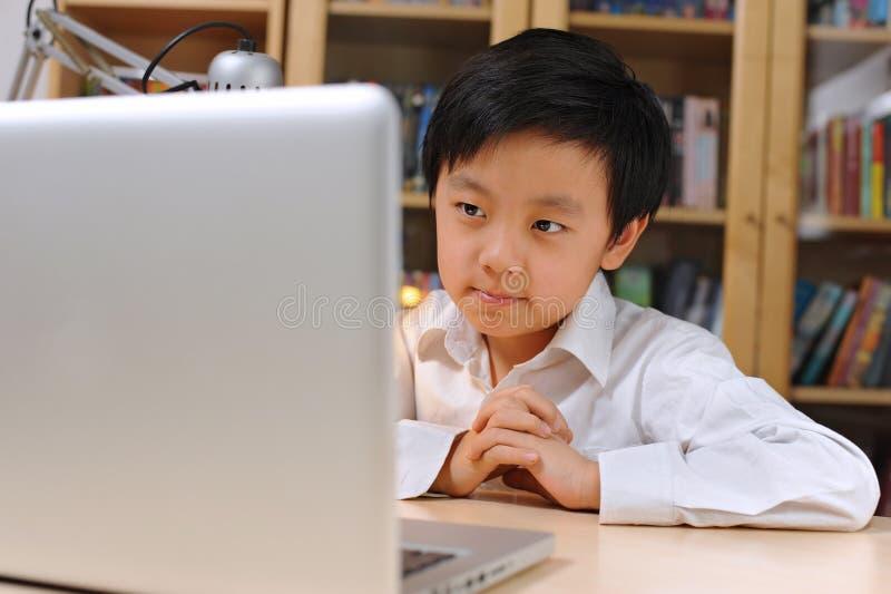 Ragazzo di banco in camicia bianca davanti al computer portatile fotografie stock