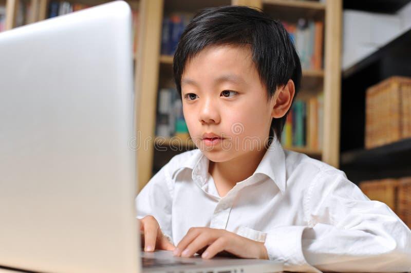 Ragazzo di banco in camicia bianca davanti al computer portatile immagini stock