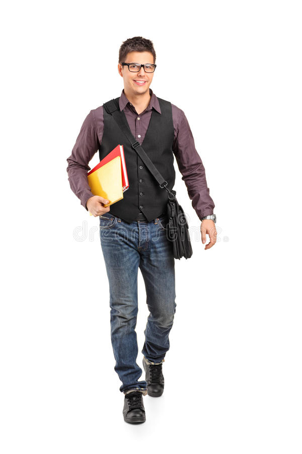 Ragazzo di banco sorridente che cammina e che tiene i libri fotografie stock