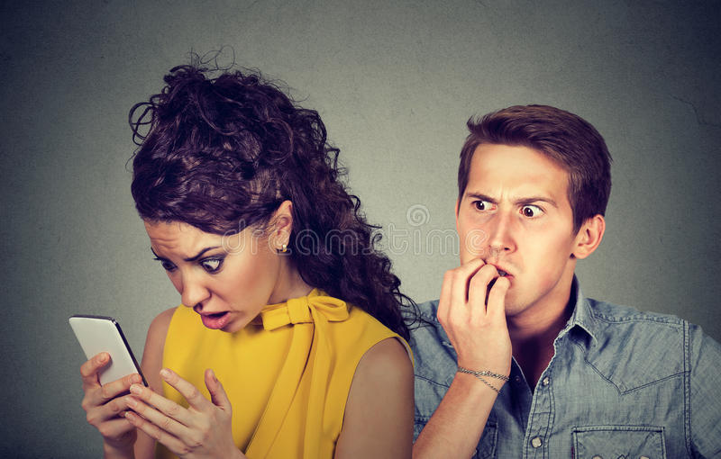 Ragazzo di frode Equipaggi le unghie nervoso mordenti mentre messaggi di testo colpiti della lettura dell'amica sul suo telefono  immagini stock libere da diritti