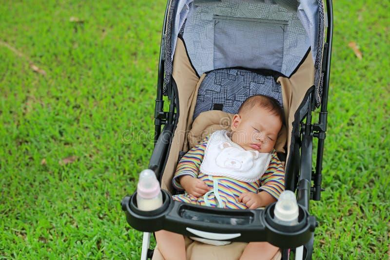 Ragazzo di neonato asiatico del primo piano che dorme in passeggiatore sul parco naturale immagini stock libere da diritti