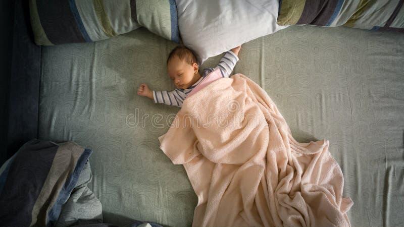 Ragazzo di neonato che si trova sul grande letto dei genitori Vista dalla parte superiore fotografie stock libere da diritti