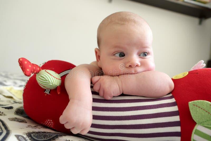 Ragazzo di neonato di pensiero che si trova su un rotolo strisciante immagini stock