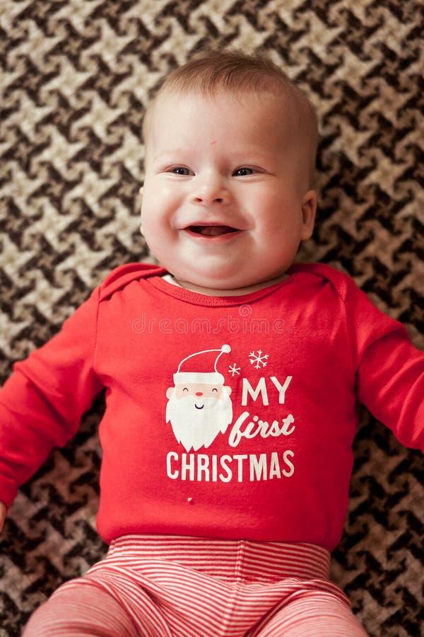 Ragazzo di neonato in pullover rosso che si trova sul tessuto e sulla vista sorridente da sopra fotografia stock