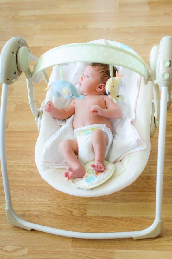 Ragazzo di neonato sveglio che si siede nell'oscillazione elettrica immagini stock
