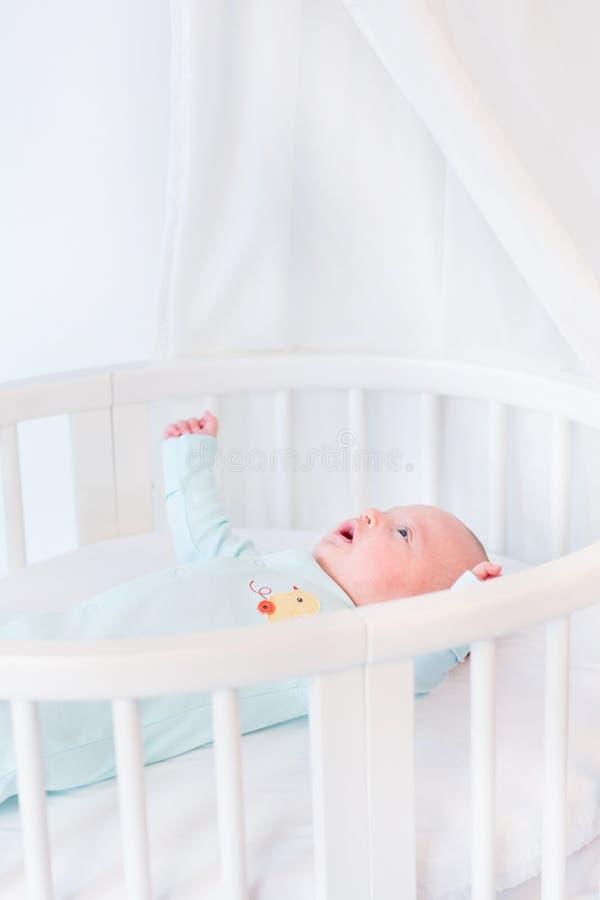 Ragazzo di neonato sveglio in letto bianco con il baldacchino fotografia stock libera da diritti