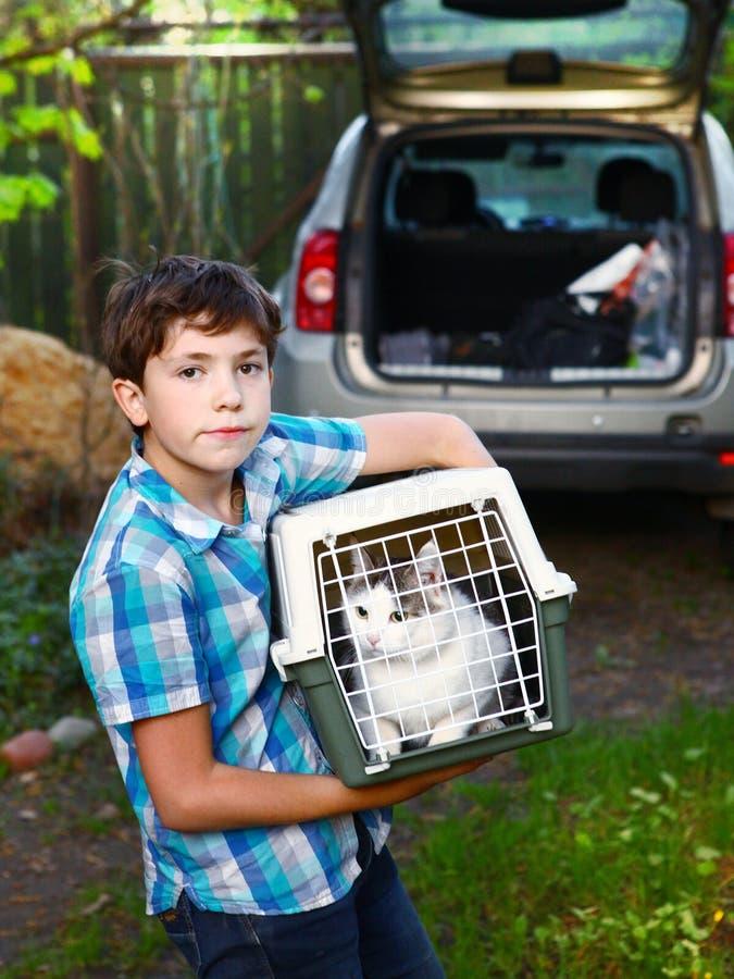 Ragazzo di paese con il gatto in trasportatore che va viaggiare automobile fotografie stock