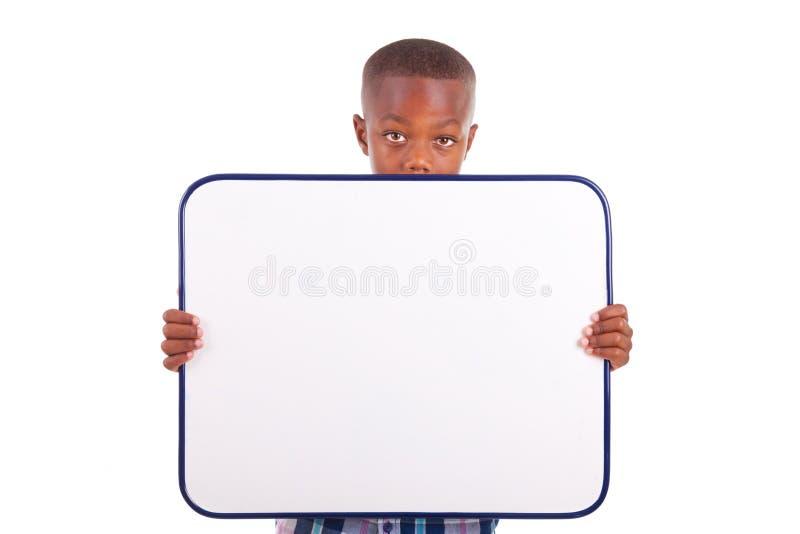 Ragazzo di scuola afroamericano che tiene un bordo in bianco - persone di colore immagine stock
