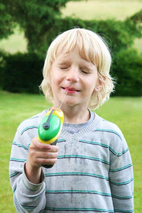 Ragazzo di scuola che gioca con la pistola a acqua all'estate fotografia stock