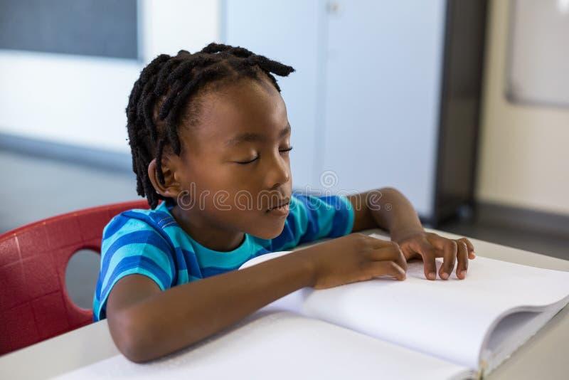 Ragazzo di scuola che memorizza la lezione in aula immagine stock libera da diritti