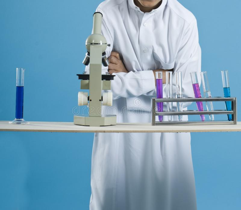 Ragazzo di scuola che utilizza un microscopio con i prodotti chimici nelle provette immagini stock