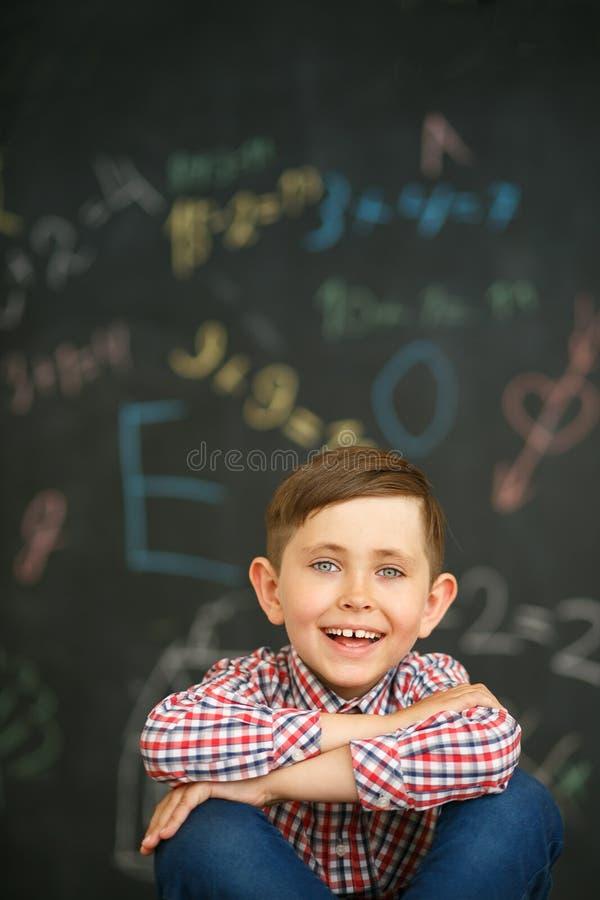 Ragazzo di scuola felice in camicia su fondo del consiglio scolastico fotografia stock libera da diritti
