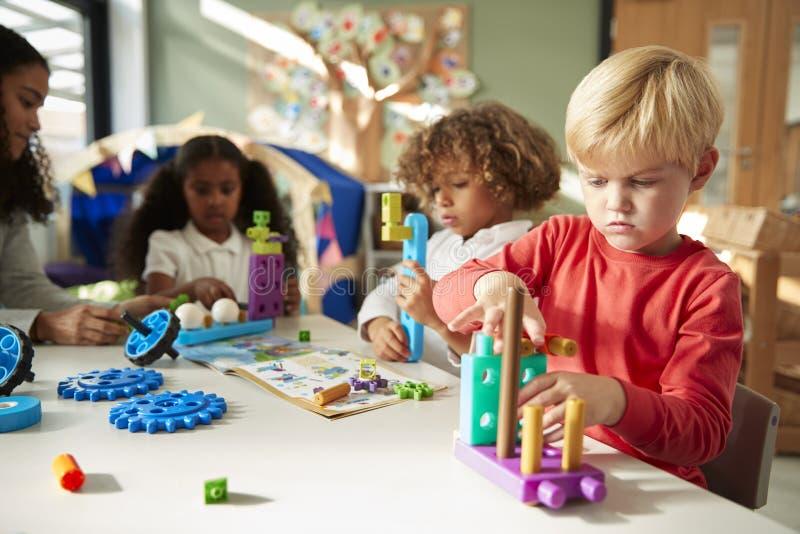 Ragazzo di scuola infantile che si siede ad una tavola facendo uso dei giocattoli educativi della costruzione con i suoi compagni immagine stock