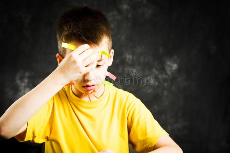 Ragazzo di scuola occupato con il suo fronte coperto negli autoadesivi fotografie stock