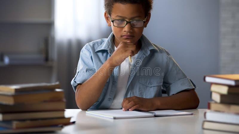 Ragazzo di scuola pensieroso che pensa al progetto di compito, scrivente saggio, istruzione fotografie stock