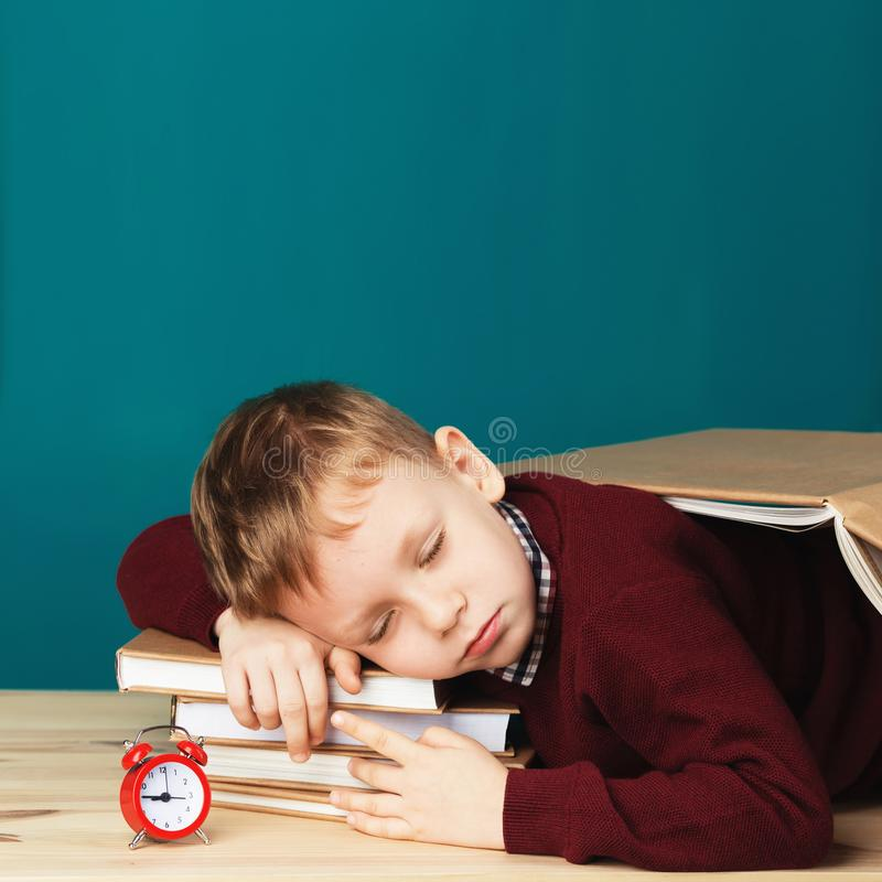 Ragazzo di scuola stanco addormentato sui libri piccolo studente che dorme sul tex immagine stock libera da diritti