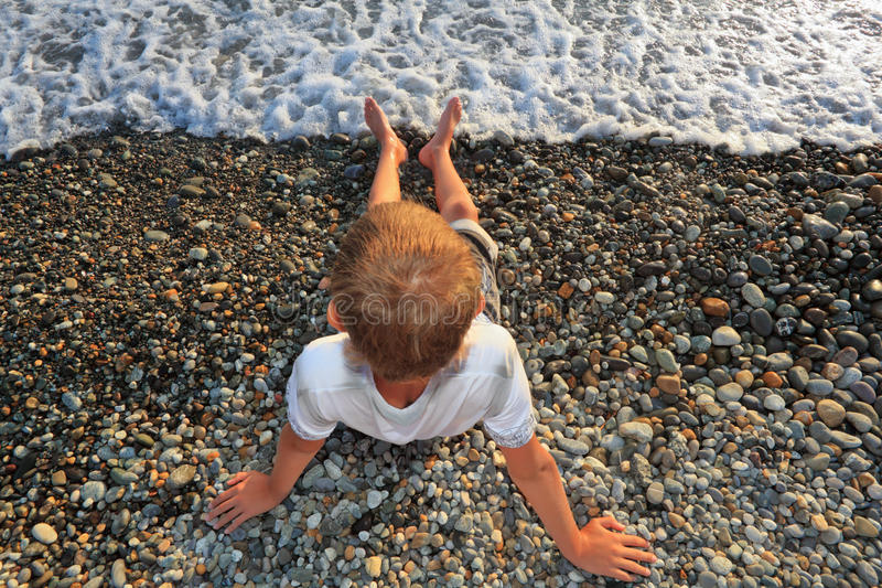 Ragazzo di seduta dell'adolescente sul litorale di pietra fotografia stock libera da diritti