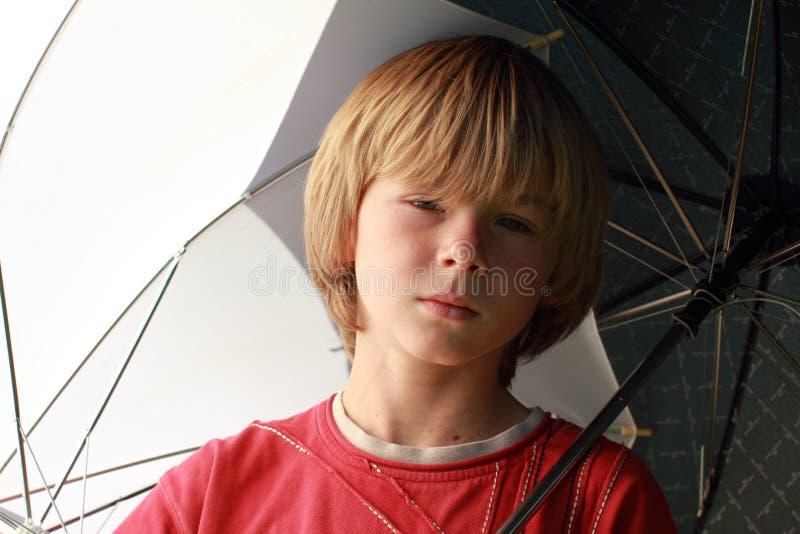 Ragazzo di Seriouse con gli ombrelli immagini stock