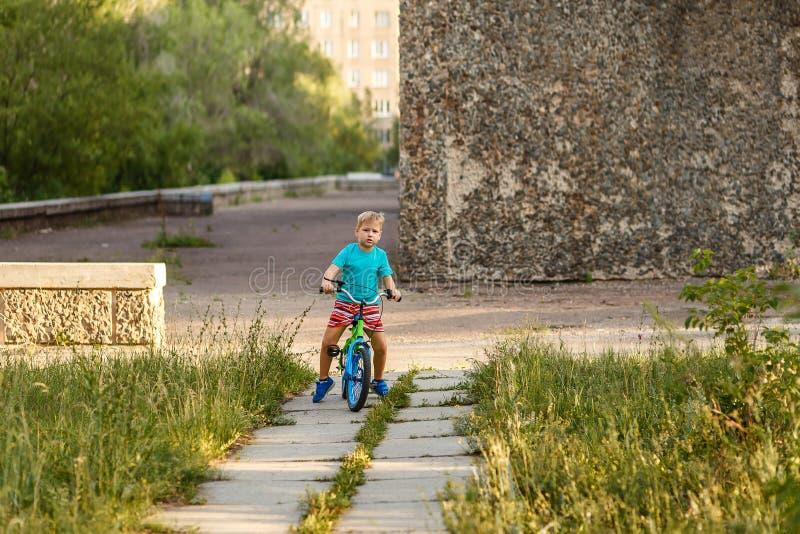 Ragazzo di sette anni serio che guida una bici nel parco della città immagini stock libere da diritti