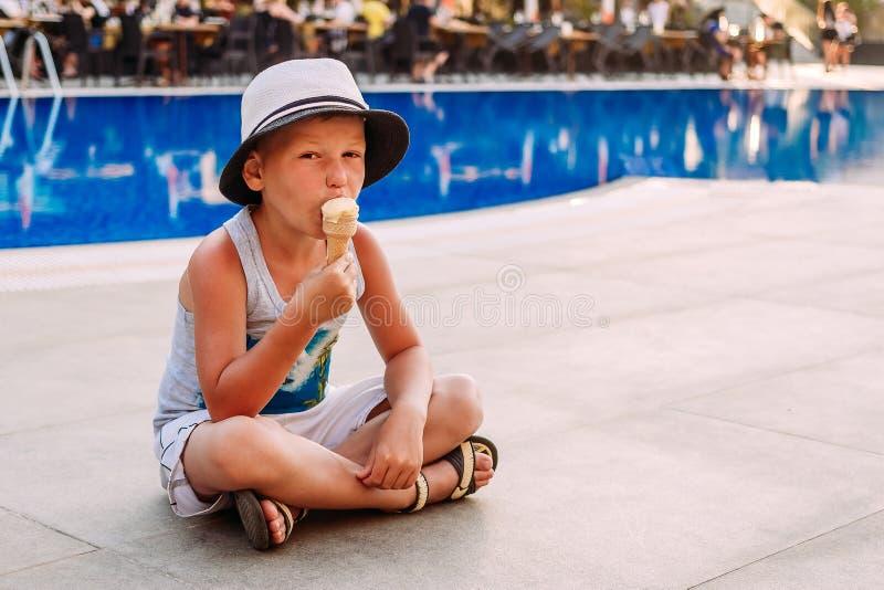Ragazzo di sette anni in un cappello che si siede dallo stagno all'aperto e che mangia il gelato in un cono della cialda immagine stock
