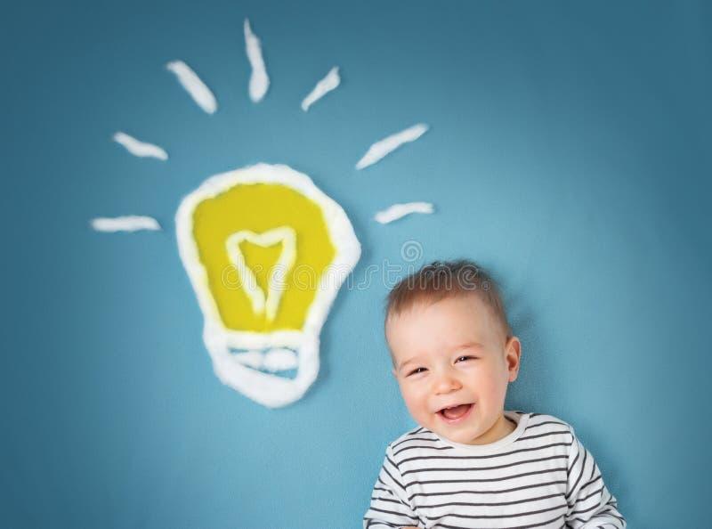 Ragazzo di un anno e una lampadina vicino Bambino con un'idea fotografia stock libera da diritti