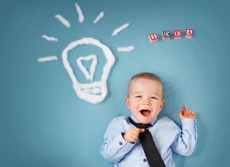 Ragazzo di un anno e una lampadina vicino Bambino con un'idea fotografia stock