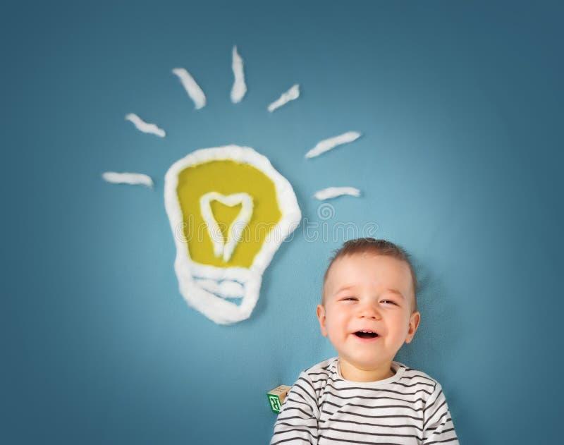 Ragazzo di un anno e una lampadina vicino Bambino con un'idea immagine stock libera da diritti
