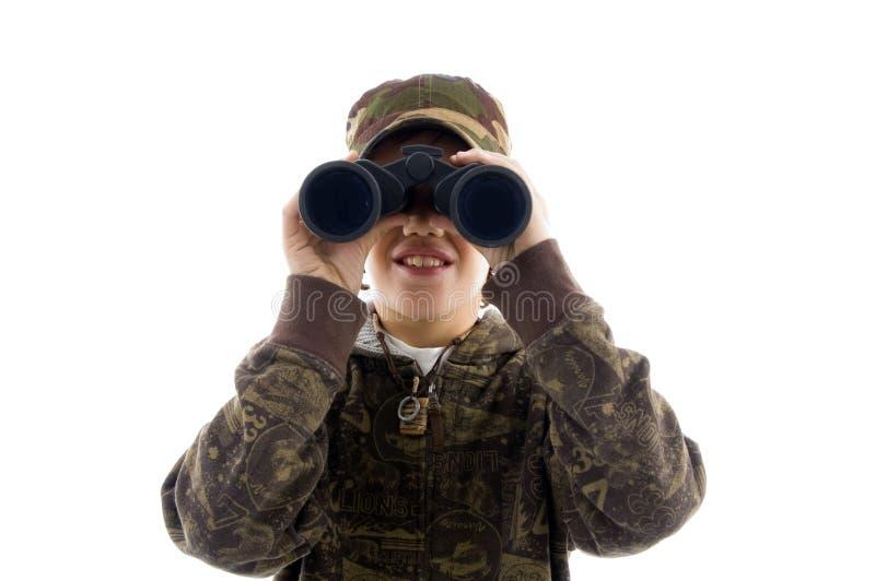 Ragazzo di vista frontale che osserva tramite il binocolo immagine stock