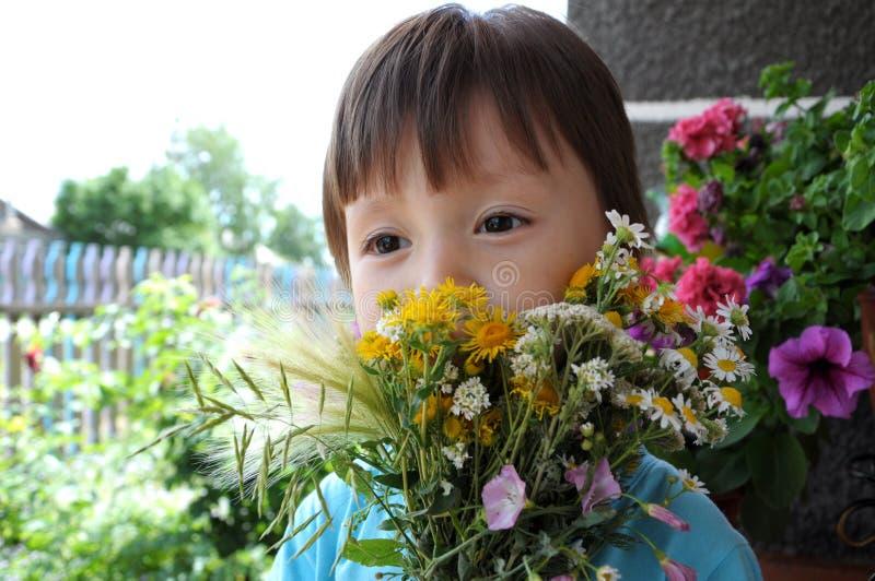 Ragazzo dietro il mazzo di estate dei wildflowers fotografia stock libera da diritti