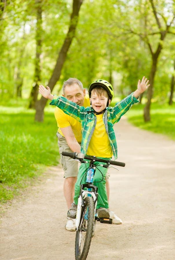Ragazzo divertendosi con suo nonno su una bicicletta fotografia stock