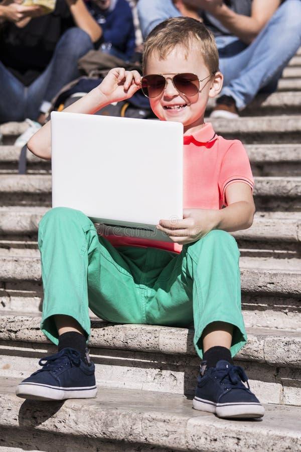 Ragazzo divertente che gioca un computer portatile di estate immagine stock
