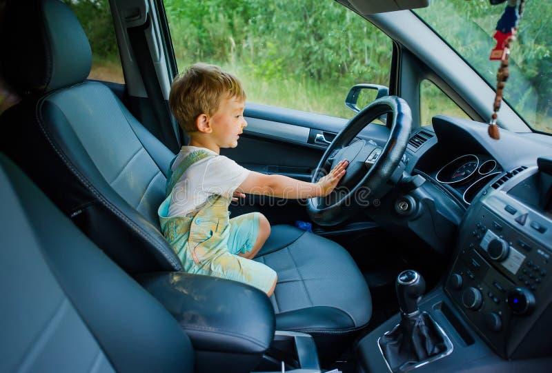 Ragazzo divertente con il fronte sporco macchiato con pittura che si tiene per mano sul volante nell'automobile fotografie stock libere da diritti