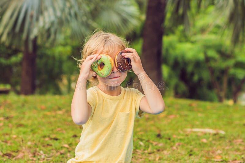 Ragazzo divertente con la ciambella il bambino sta divertendosi con la ciambella Alimento saporito per i bambini Tempo felice all fotografia stock