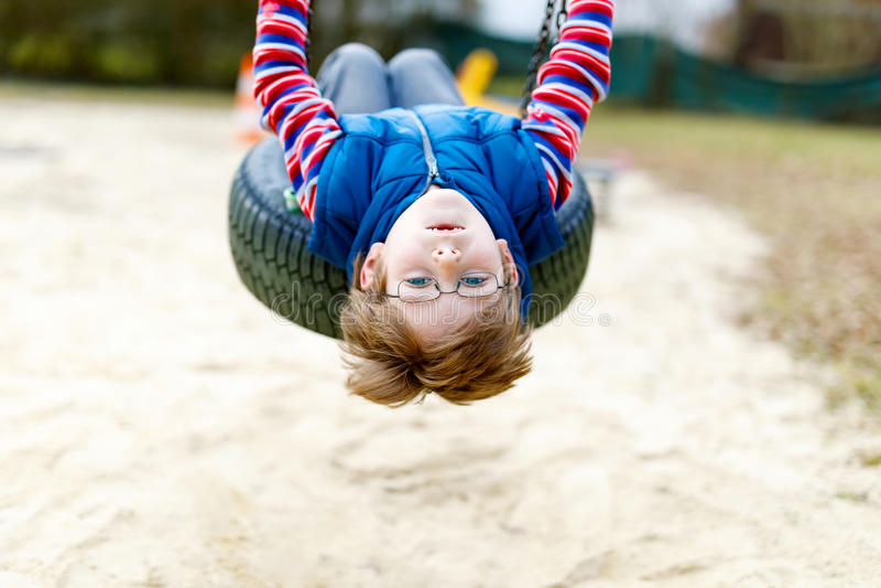Ragazzo divertente del bambino divertendosi con l'oscillazione a catena sul campo da giuoco all'aperto immagini stock