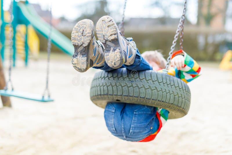 Ragazzo divertente del bambino divertendosi con l'oscillazione a catena sul campo da giuoco all'aperto fotografia stock libera da diritti