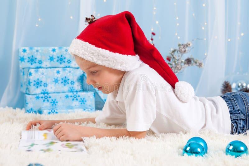 Ragazzo dolce, leggente un libro sul Natale, decorazione intorno lui fotografia stock