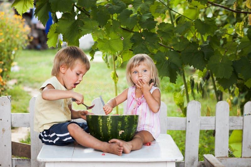 Ragazzo e bambina felici con la menzogne dell'anguria immagine stock