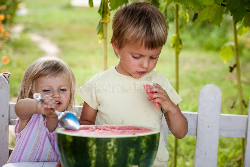 Ragazzo e bambina felici con la menzogne dell'anguria fotografia stock