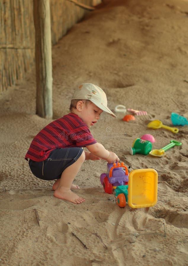 Ragazzo e giocattoli sulla spiaggia fotografia stock