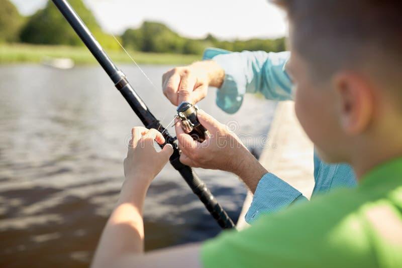 Ragazzo e nonno con la canna da pesca sul fiume immagine stock