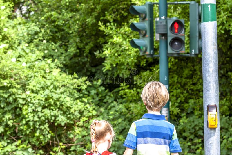 Ragazzo e ragazza che aspettano al semaforo rosso immagine stock libera da diritti