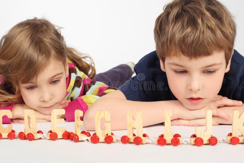Ragazzo e ragazza che giocano con la ferrovia di alfabeto fotografie stock