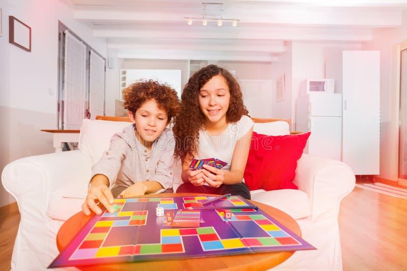 Ragazzo e ragazza che giocano gioco da tavolo a casa fotografia stock