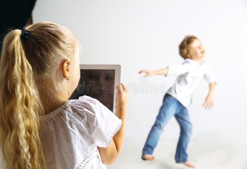 Ragazzo e ragazza che giocano insieme sul fondo bianco dello studio immagini stock libere da diritti