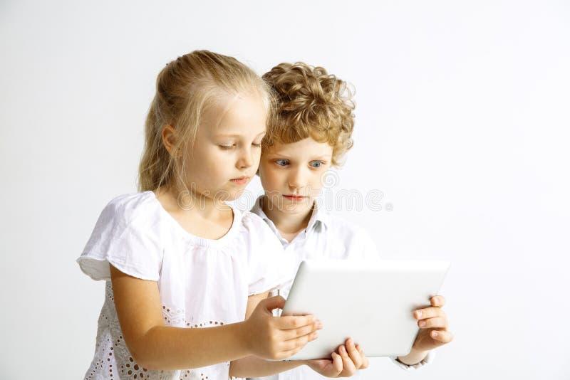 Ragazzo e ragazza che giocano insieme sul fondo bianco dello studio immagine stock