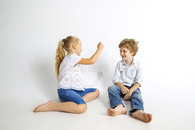Ragazzo e ragazza che giocano insieme sul fondo bianco dello studio fotografie stock