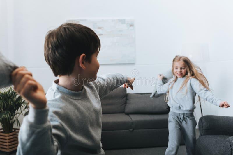 Ragazzo e ragazza che giocano lotta di cuscino a casa immagini stock