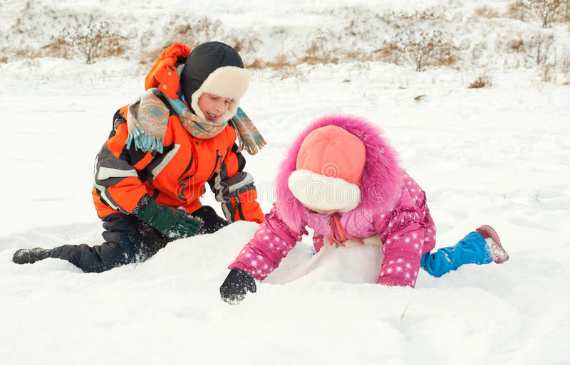 Ragazzo e ragazza che giocano sulla neve fotografia stock
