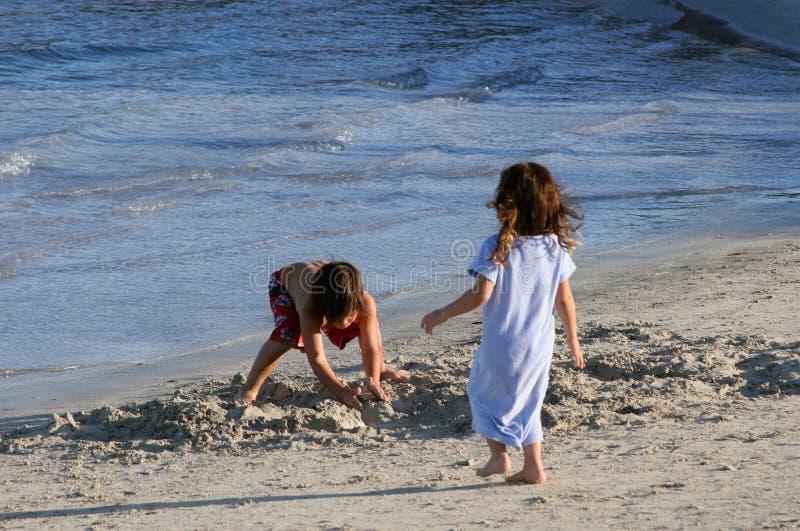 Ragazzo e ragazza che giocano sulla spiaggia. immagine stock