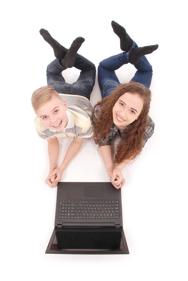 Ragazzo e ragazza che per mezzo di un computer portatile che si trova sul pavimento fotografie stock